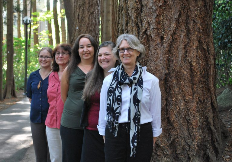 Xwi7xwa Library staff members in front of tree